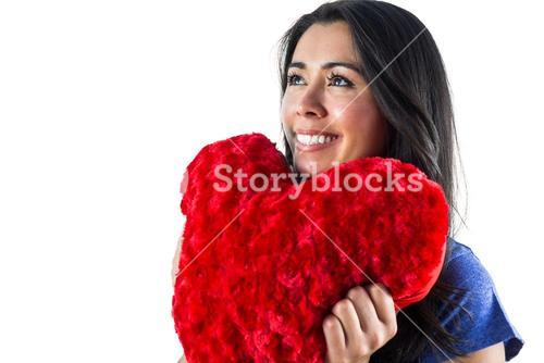 Smiling woman holding a heart shaped pillow