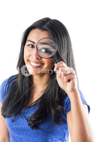 Happy woman using a magnifying glass