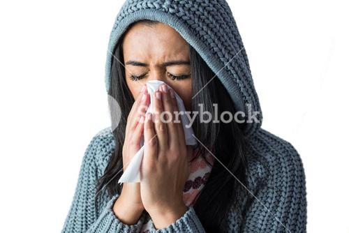 Woman sneezing into her tissue