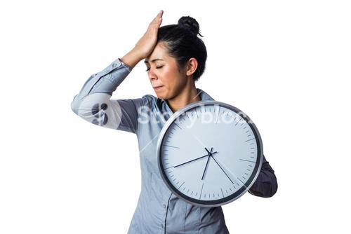 Woman slapping her forehead and holding a clock