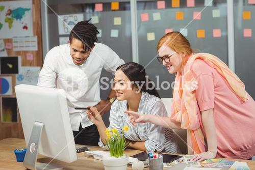Smiling business people using computer in office