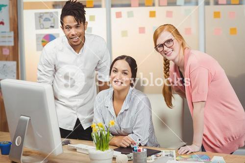 Smiling business people at desk
