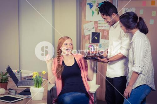 Surprised woman seeing birthday cake