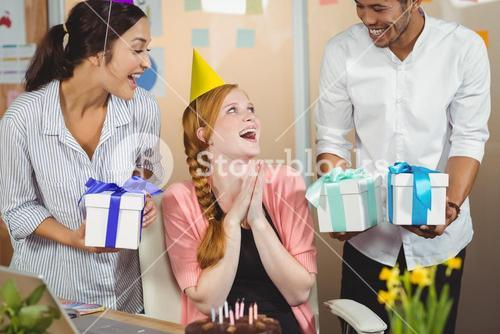 Happy colleagues with gifts looking at businesswoman