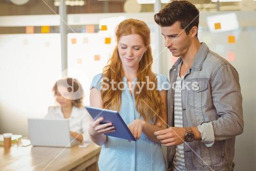 Businesswoman showing digital PC to businessman