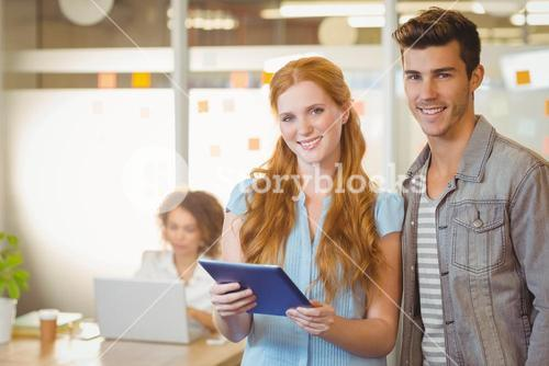 Portrait of business people holding digital PC