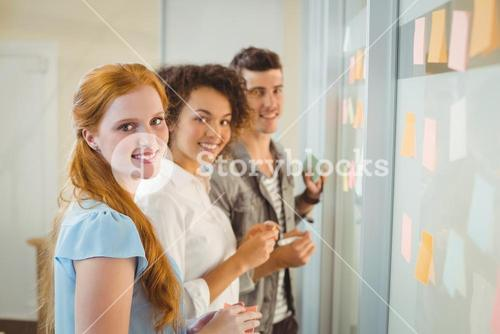 Portrait of smiling business people standing by glass wall