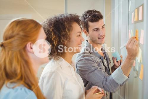 Businessman writing on glass wall as female colleagues looking at it
