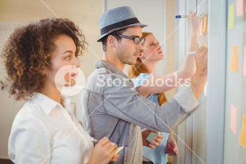 Business people writing on adhesive notes on glass wall