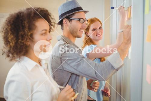 Businesswoman writing on adhesive notes on glass wall with colleagues