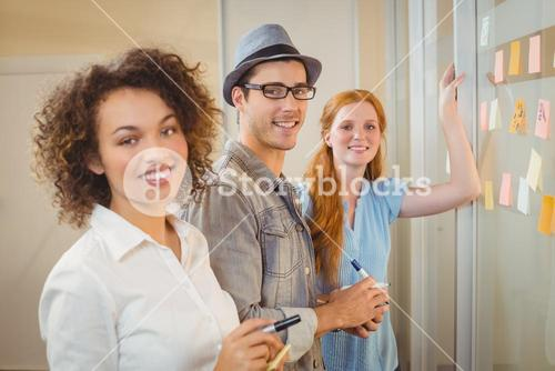 Portrait of happy business people standing by glass wall