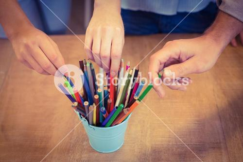 Business people choosing pencils from desk organizer
