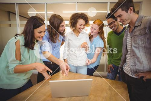 Business people pointing at laptop