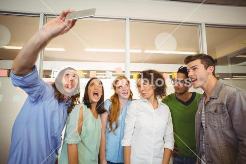 Business people taking selfie while making face