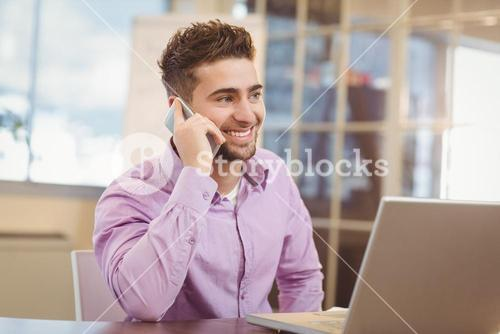 Businessman calling on phone in office