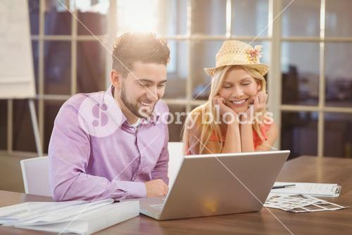 Business woman wearing hat sitting by male colleague