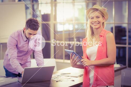 Businesswoman with digital tablet by male colleague working on laptop