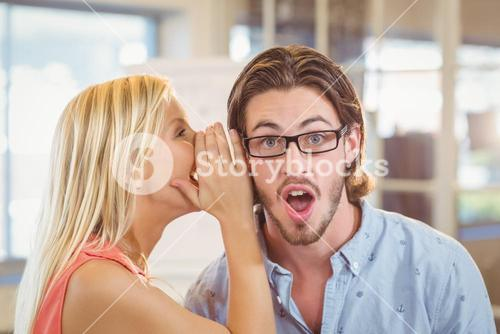 Businessman listening to rumor which female colleague is whispering