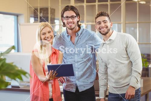 Smiling business people with digital tablet