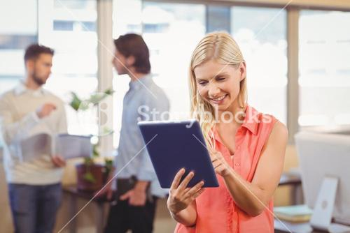 Smiling businesswoman using digital PC in office