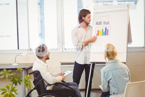 Businessman explaining multi colored graph to colleagues