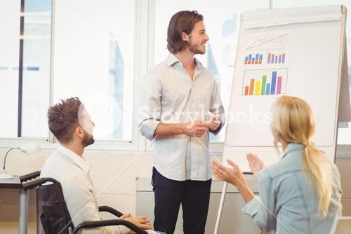 Business people with male colleague looking at multi colored graph