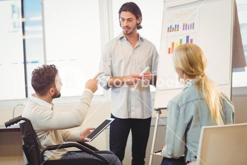 Disabled businessman pointing towards whiteboard