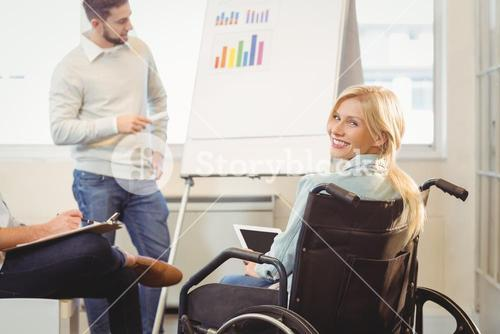 Disabled businesswoman on wheelchair holding digital tablet