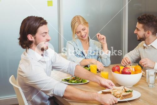 Businessman holding plate of sandwich