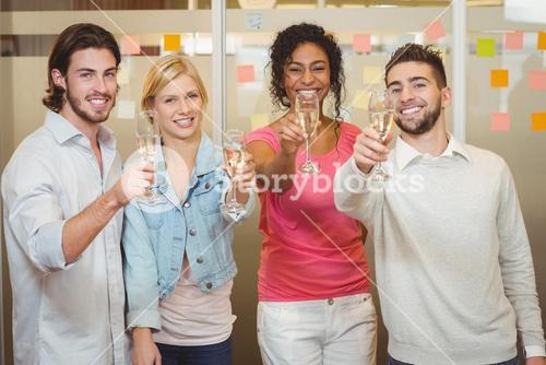 Happy colleagues holding champagne flute in party
