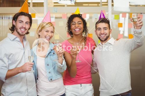 Colleagues holding champagne flute in birthday party