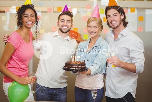 Smiling colleagues enjoying birthday party