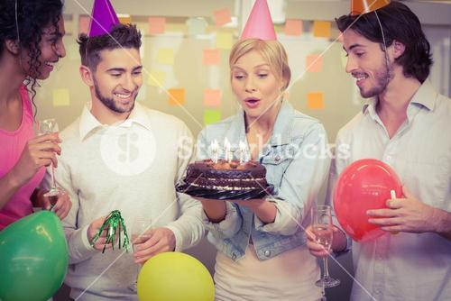 Businesswoman blowing birthday candles