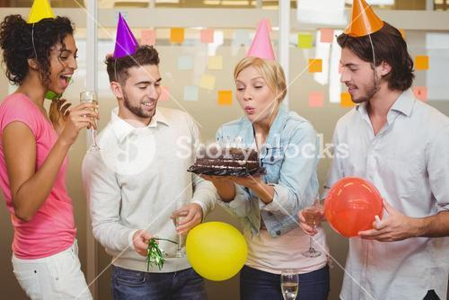 Businesswoman blowing birthday candles in office