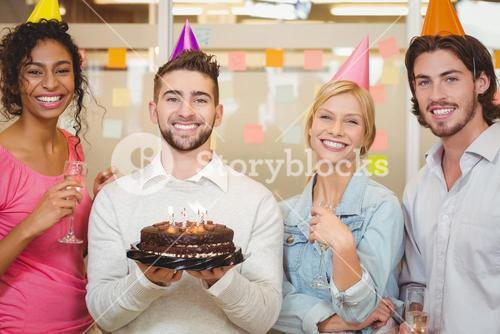 Smiling business people with birthday cake