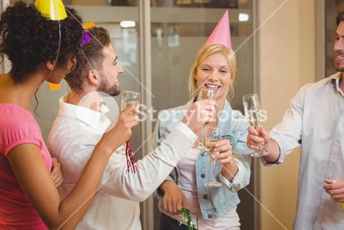 Colleagues toasting champagne in birthday party