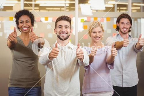Portrait of smiling business team gesturing thumps up in office