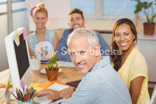 Business people sitting by desk with computer