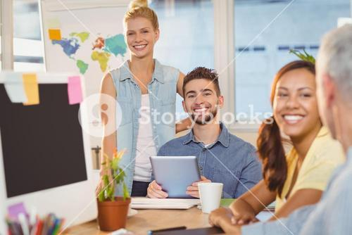 Smiling business people using digital PC