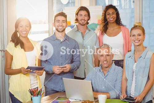 Smiling business people with technologies in meeting room