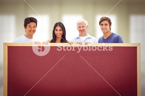 Composite image of people in jeans holding a big sign