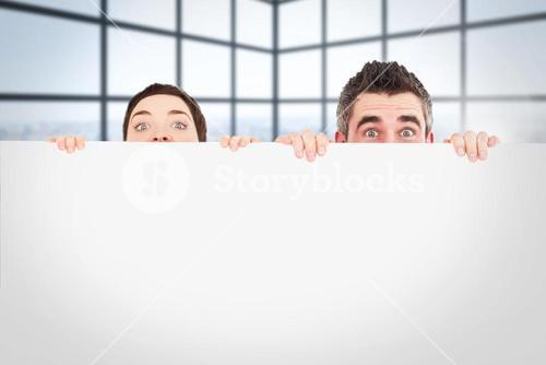 Composite image of man and woman hiding behind a white board with room for  copy space