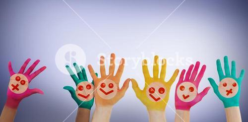 Composite image of hands with colourful smiley faces