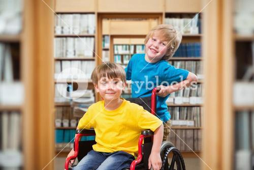 Composite image of happy boy pushing friend on wheelchair