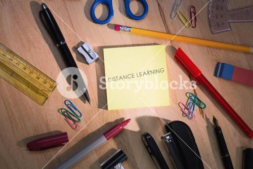 Distance learning against students table with school supplies