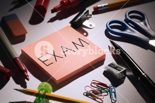 Exam against students table with school supplies