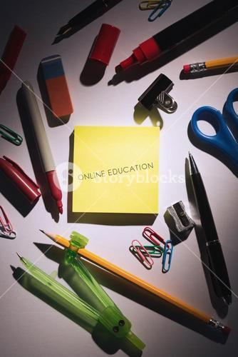 Online education against students table with school supplies