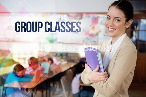 Group classes against pretty teacher smiling at camera at back of classroom