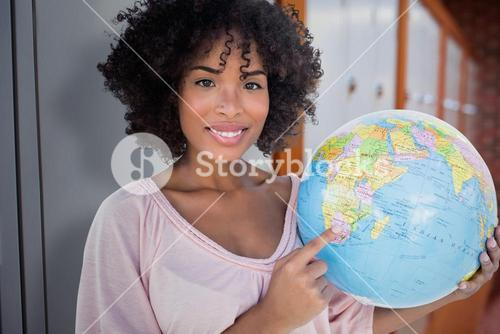Composite image of happy woman pointing to globe