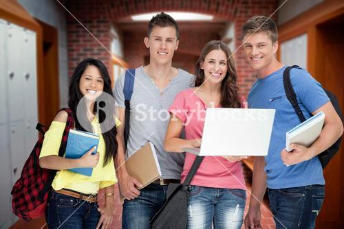 Composite image of a smiling group of students holding a laptop while looking at the camera